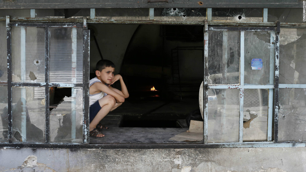 A boy sits at a window spotted with bullet holes at a local bakery.