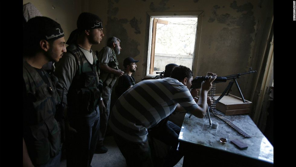 Free Syrian Army fighters take up positions in a shelled out building in the Seif El Dawla neighborhood of Aleppo on Sunday, September 2, as clashes with Syrian government forces continue.