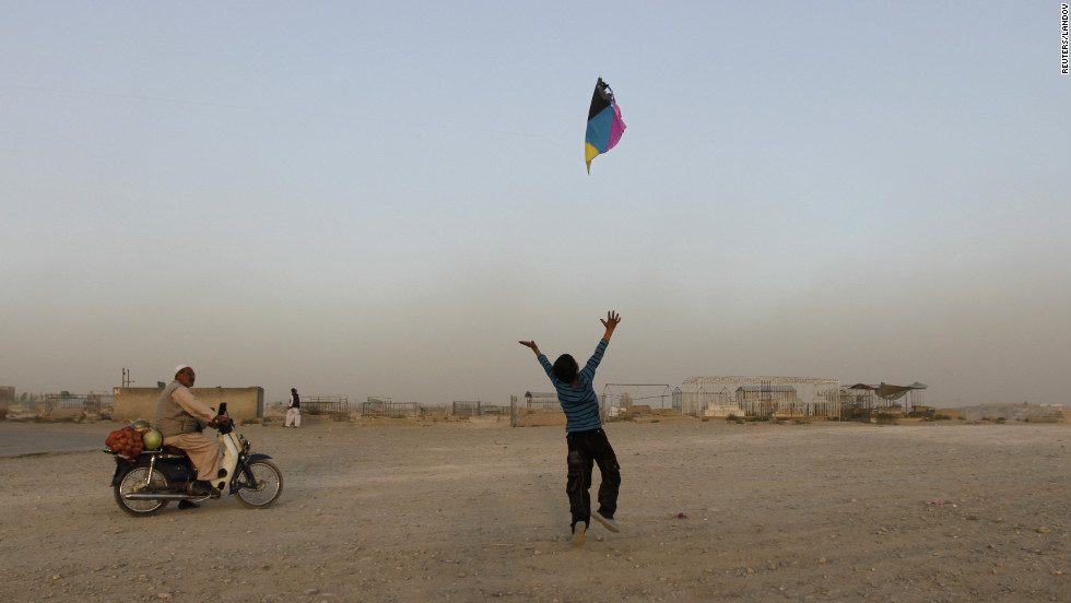 An Afghan boy tries to catch a falling kite on a hilltop Monday in Kabul.