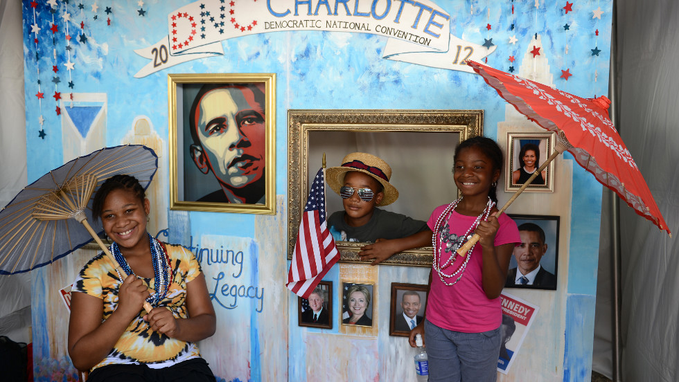 Michah Robinson poses with his sister Simone and cousin Lanise Myers in a souvenir photo booth at the CarolinaFest street festival on Monday.