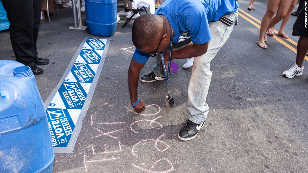 A man writes in chalk to promote a voter registration booth during the DNC on Monday.