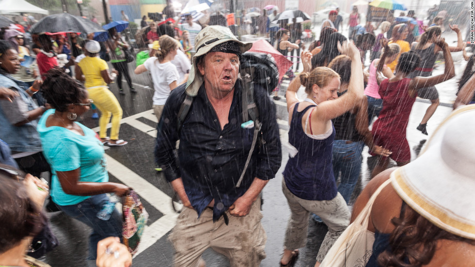 People dance in the rain Monday in the streets of Charlotte.