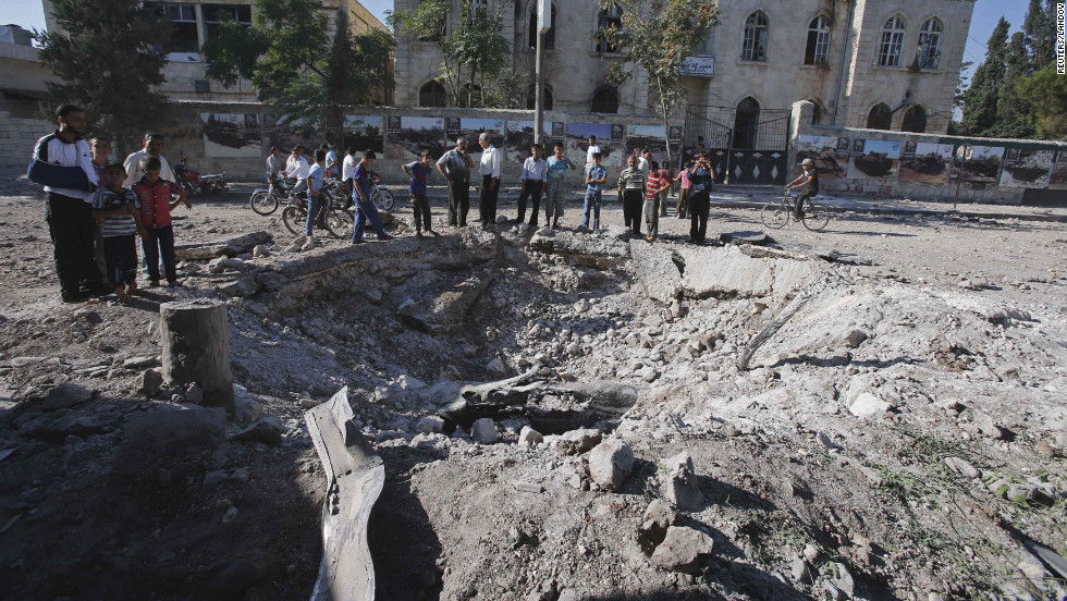 Civilians stand near a bomb crater after a Syrian air force fighter jet dropped a bomb on Wednesday, September 5, in Azaz, a town north of Aleppo.