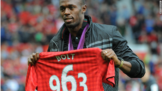 Usain Bolt shows off a special Manchester United shirt bearing his winning time in the 2012 Olympic 100m final.