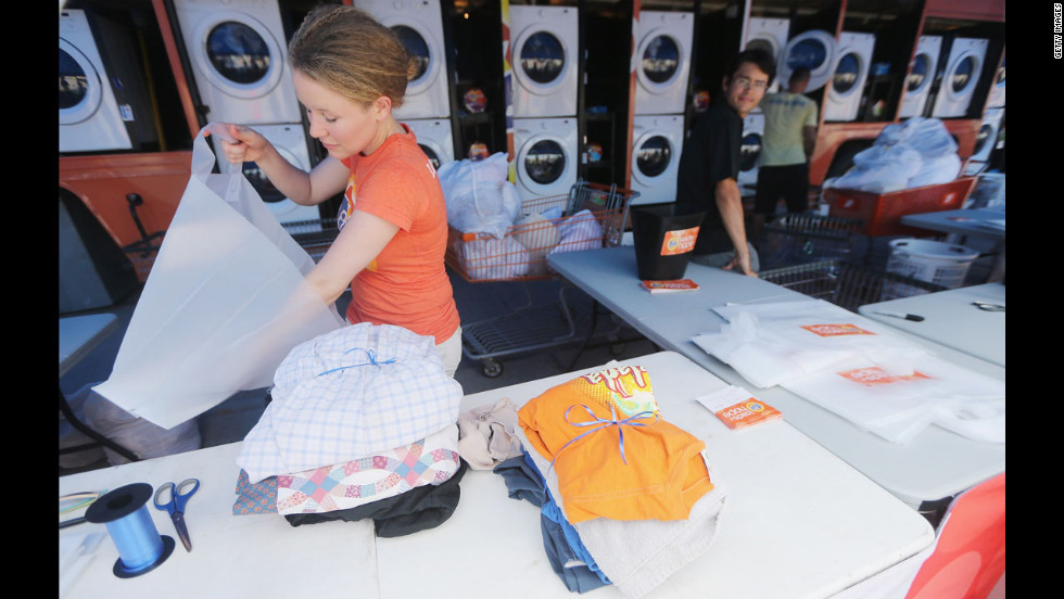 Worker Holly Rochelle sorts a resident's laundry, washed for free at the Tide Loads of Hope mobile laundromat set up for those affected by Isaac, on Thursday in LaPlace.