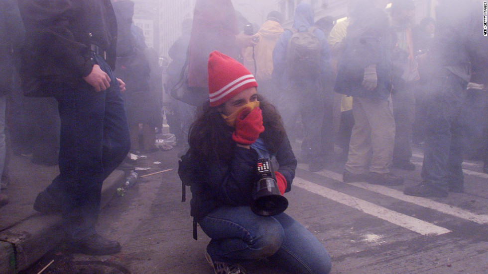 <strong>1999: </strong>A demonstrator covers her mouth with a scarf to protect herself from tear gas after street clashes with riot police in downtown Seattle during WTO protests.