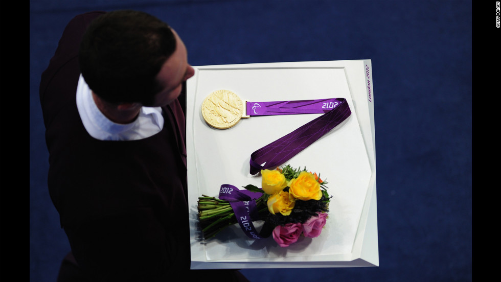 A medal bearer carries a medal and flowers on Friday.