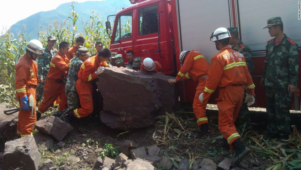 Rescuers remove a rock from a road in Yiliang.