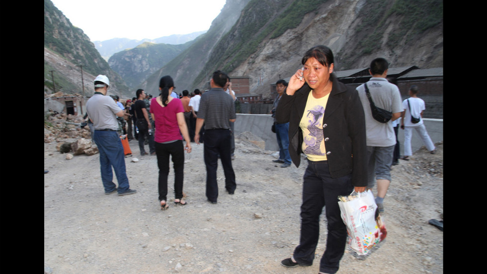 A woman cries while she makes a phone call on a blocked road in Yiliang, Yunnan province.