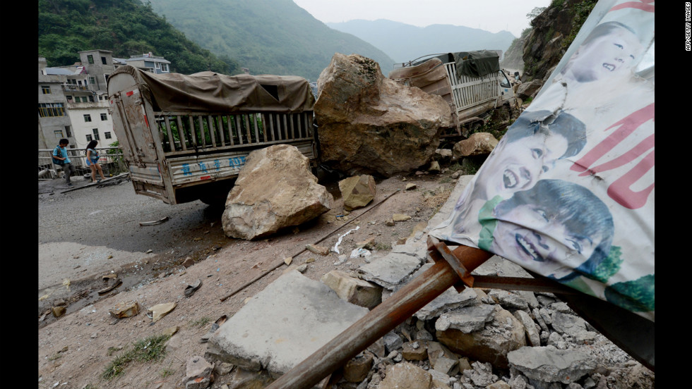 Local residents walk past destroyed vehicles at a landslide area on Saturday.
