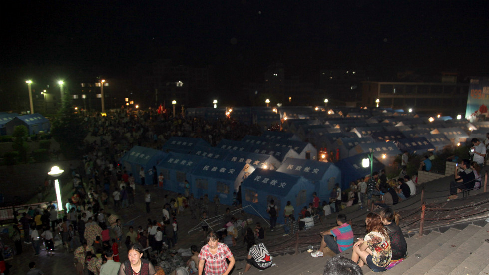 Residents rest by the makeshift tents (back) at an emergency relief center set up in the town square in Yiliang.