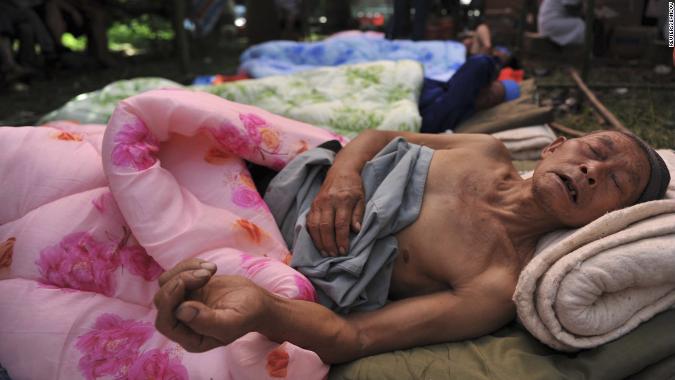 A injured person lies in bed at a temporary hospital on Saturday.