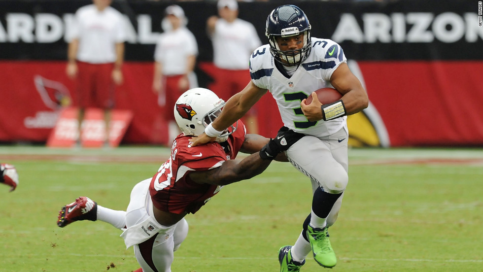 No. 3 Russell Wilson of the Seahawks avoids a tackle by No. 50 O'Brien Schofield of the Cardinals on Sunday.