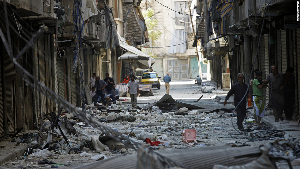 Residents walk down a street covered in rubble in the neighborhood of Bustan al-Basha on Saturday.