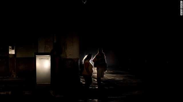 People walk down a dark street during a blackout in Havana, Cuba, on Sunday. Some six provinces in the country experienced the blackout.