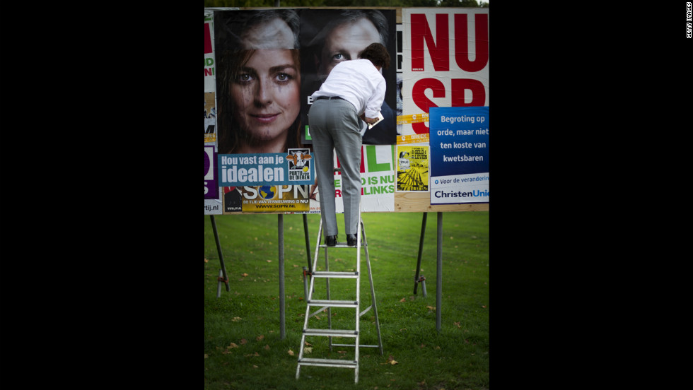 A worker hangs a poster of one the many parties taking part in Wednesday's Dutch parliamentary elections in Utrecht, Netherlands, on Monday.
