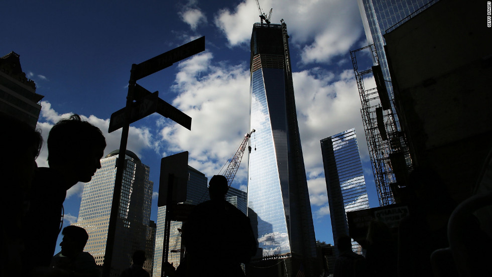 Pedestrians walk by One World Trade Center on the eve of the 11th anniversary of the September 11 terrorist attacks on September 10, 2012, in New York City.