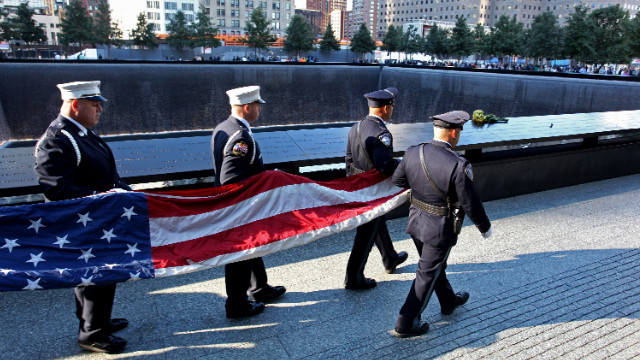 NEW YORK - SEPTEMBER 11:  An honor guard carries the World Trade Center flag near the South Pool of the 9/11 Memorial during ceremonies for the eleventh anniversary of the terrorist attacks on lower Manhattan at the World Trade Center site September 11, 2012 in New York City. New York City and the nation are commemorating the eleventh anniversary of the September 11, 2001 attacks which resulted in the deaths of nearly 3,000 people after two hijacked planes crashed into the World Trade Center, one into the Pentagon in Arlington, Virginia and one crash landed in Shanksville, Pennsylvania. (Photo by Craig Ruttle-Pool/Getty Images)