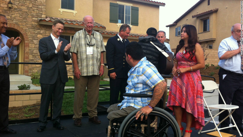 Dominguez, with his wife Alexis, is cheered by Temecula Mayor Chuck Washington (from left), actor Gary Sinise, Ned Wallace, Ret. FDNY Battalion Chief John Carroll, and Jim Shubert during the presentation of his new 'smart' home on September 11, 2012.