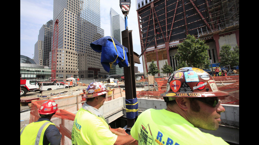 Construction workers watch as the cross is lowered by crane into a subterranean section of the 9/11 Memorial and Museum on July 23, 2011.
