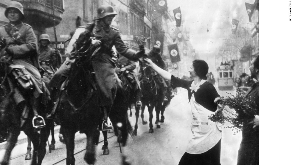 German Nazi leader Adolf Hitler violates the Locarno Pact and the Treaty of Versailles on March 7, 1936, by sending German forces, seen here receiving flowers by well-wishers, to the demilitarized Rhineland.