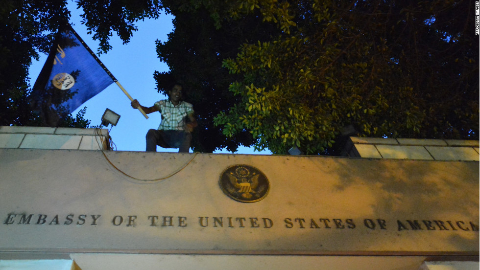 "An Egyptian protester waves a black flag inscribed with the Muslim profession of faith -- ""There is no God but God, and Mohammed is the prophet of God"" -- as he stands above the door of the U.S. Embassy."
