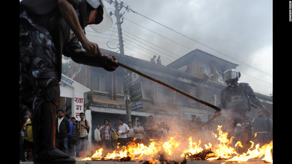 Nepalese people put out a fire lit by student activists Tuesday during a protest against the hike in the fuel price in Kathmandu and demanding the resignation of Prime Minister Baburam Bhattarai. Student groups have threatened to call a general strike in Kathmandu on Wednesday.