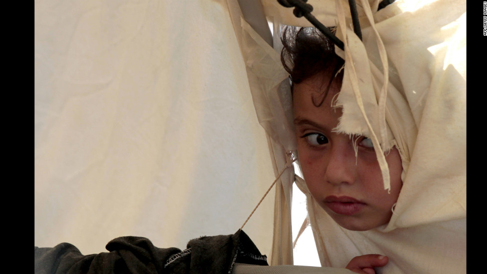 "A Syrian refugee girl peeks through a hole in a tent at the Zaatri refugee camp near the Jordanian border with Syria, on Tuesday, September 11. The number of refugees who have fled Syria has reached more than 250,000, the United Nations said, calling the humanitarian problems sparked by the civil war ""our biggest crisis""."