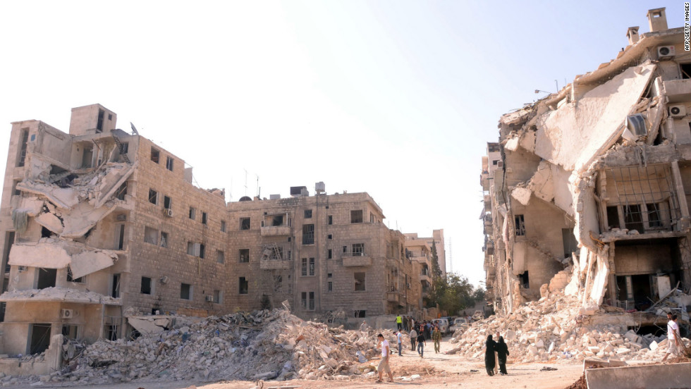 People walk past a row of destroyed buildings near the Al-Hayat Hospital in Aleppo on Monday.
