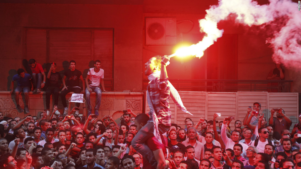 People shout and light flares in front of the U.S. Embassy in Cairo.
