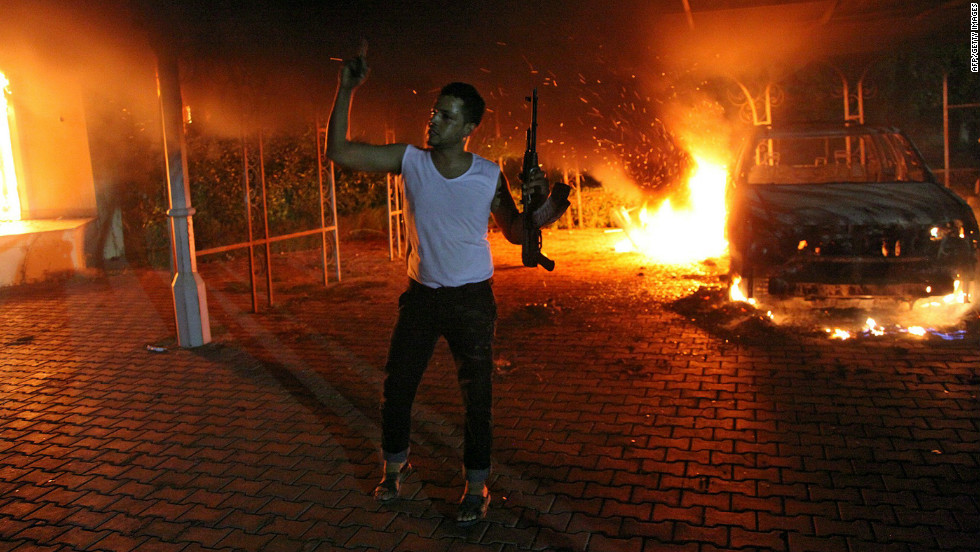 A man waves his rifle as buildings and cars are engulfed in flames inside the U.S. Consulate compound in Benghazi, Libya, late on Tuesday, September 11.