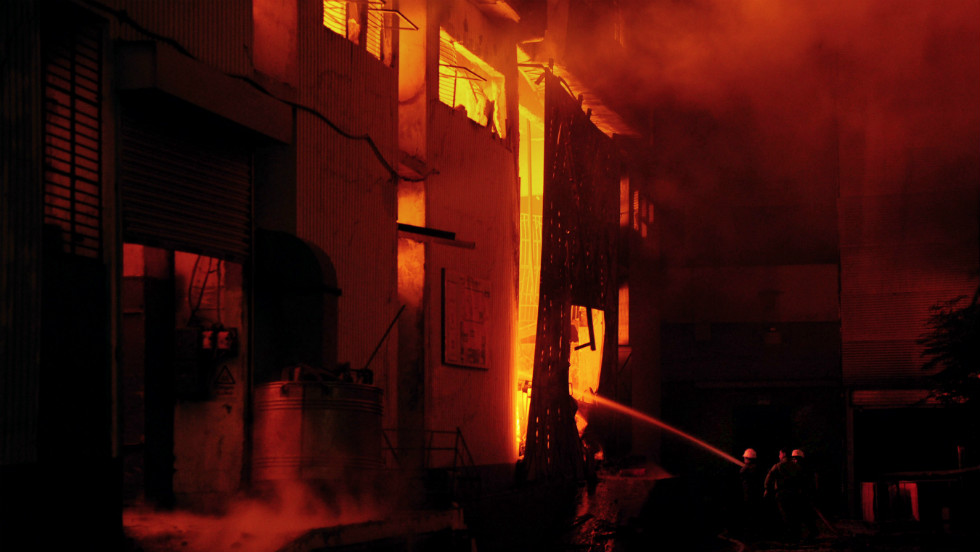 Pakistani firefighters extinguish a fire that erupted in a garment factory.  At one stage, firefighters feared dozens of people were trapped in the building's basement.