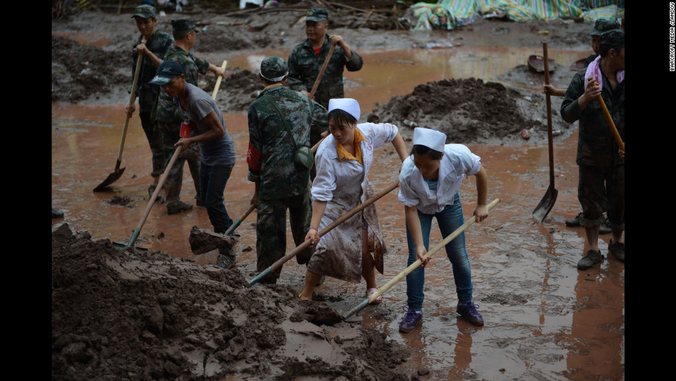 Nurses join soldiers to clear mud and debris from the hospital on Monday.