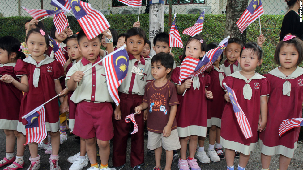 Schoolchildren wave Malaysia national flags as Britain's Prince William and his wife Catherine, the Duchess of Cambridge, arrive at the Hospis Malaysia in Kuala Lumpur on September 13, 2012.