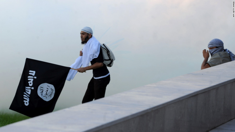 A Tunisian protester holds an Al-Qaeda affiliated flag amid the smoke coming from the tear gas fired by riot police outside the U.S. Embassy in Tunis on Friday.