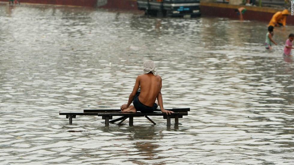 A resident rests on a flooded street in Paranaque.