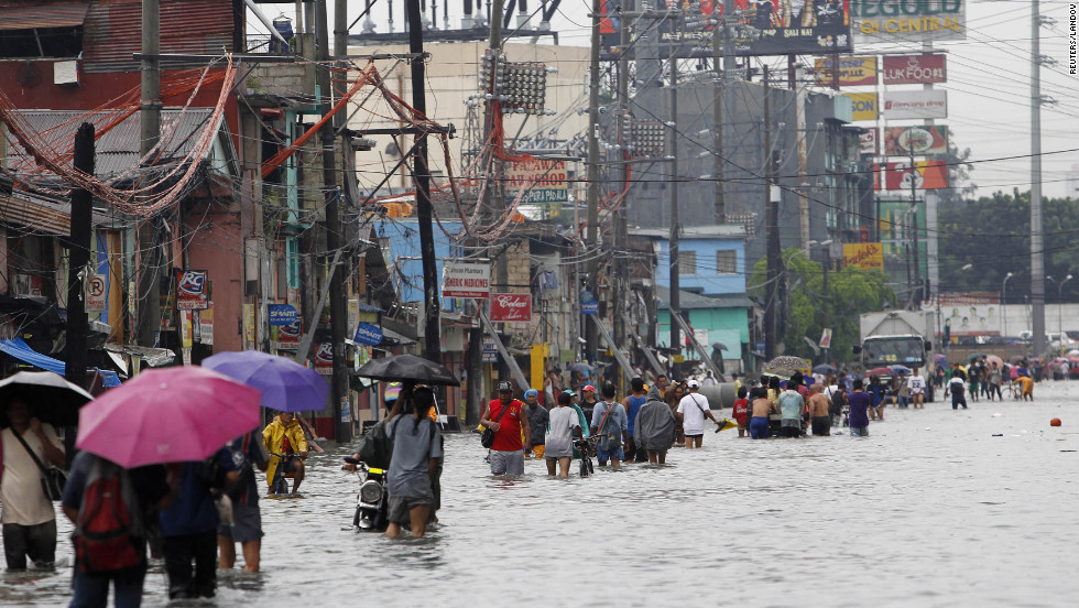 Commuters wade through a flooded street Saturday during a heavy downpour in Quezon City, in metro Manila.