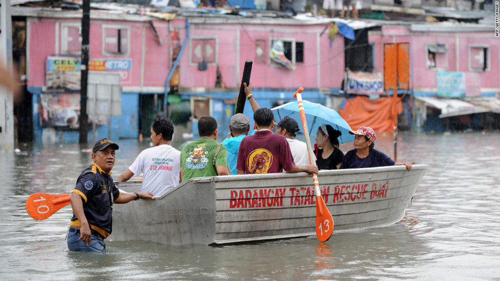 Residents ride on a boat near their flooded homes in Manila.