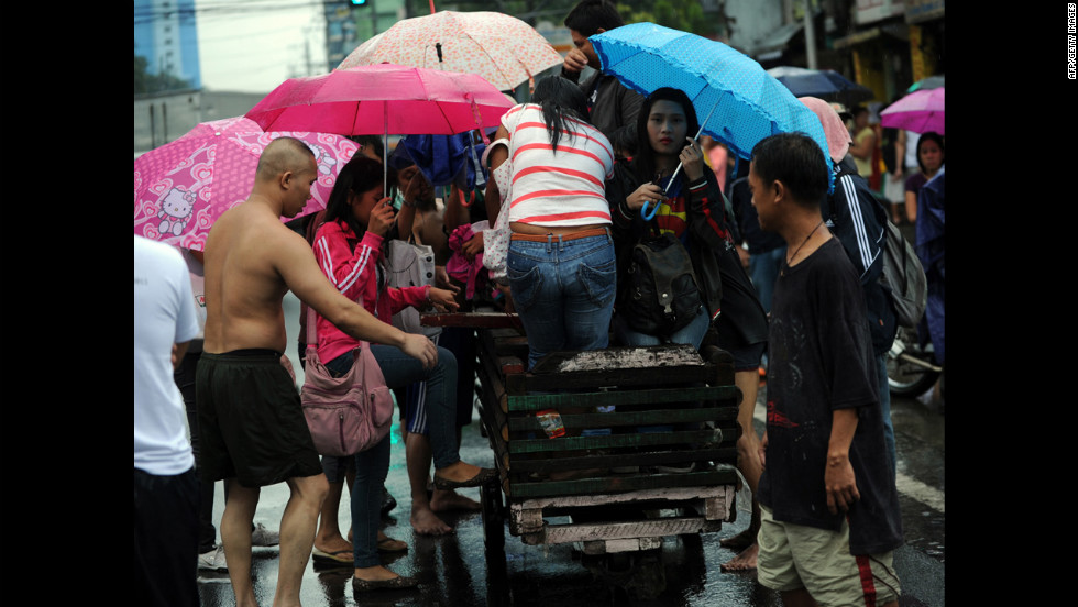 Stranded passengers are transported on a wooden pushcart in Manila.