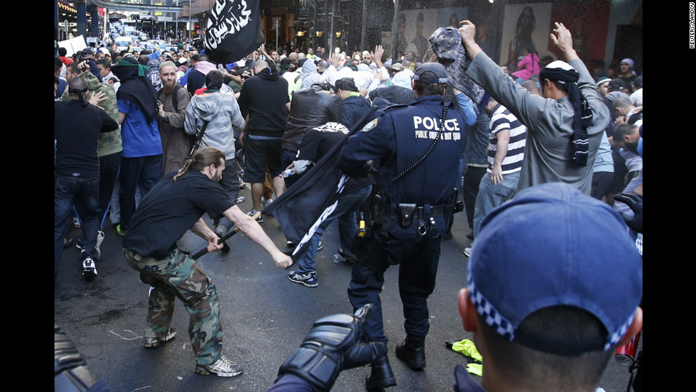 "A protester hits a policeman with a pole in Sydney's central business district on Saturday, September 15. Anger over an anti-Islam video, ""The Innocence of Muslims,"" spread to Australia on Saturday, and protesters took to the streets of the country's capital."