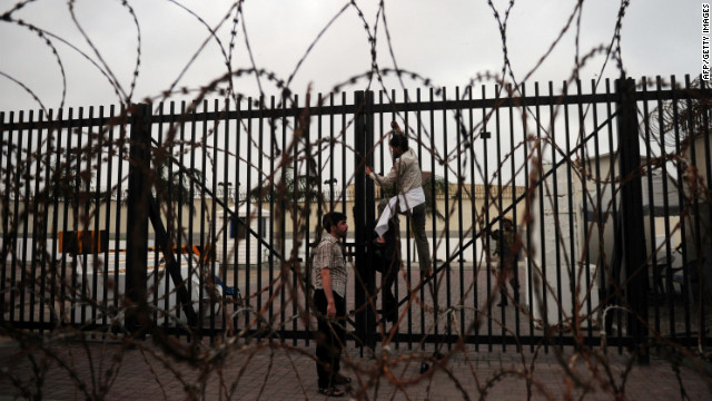 A Pakistani Shiite Muslim protester climbs on a gate of the U.S. Consulate in Karachi on Sunday.