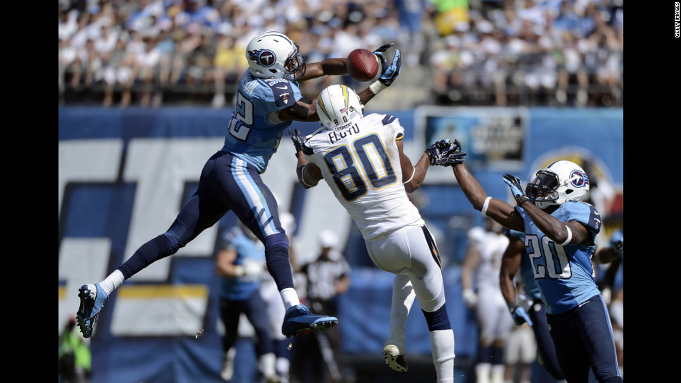 Robert Johnson of the Tennessee Titans, left, tips the ball past the hands of Malcom Floyd of the San Diego Chargers into the hands of Alterraun Verner, right, for an interception on Sunday.
