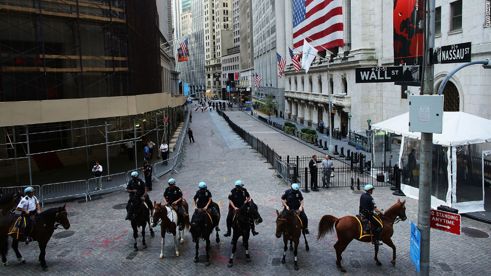Police on horseback stand guard along Wall Street on Monday.