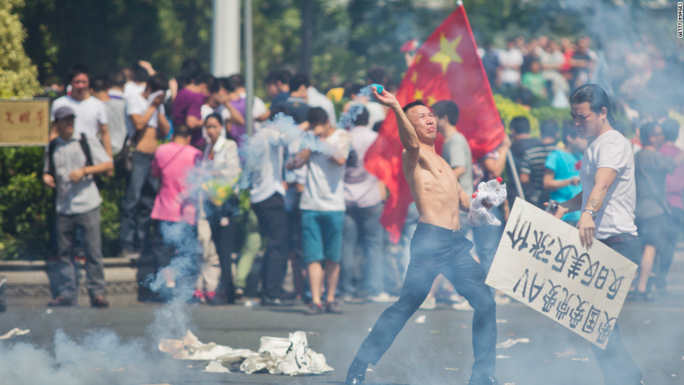 A protester hurls a gas cannister during a demonstration in Shenzhen, China on September 16, over the disputed Diaoyu Islands, which is also known as Senkaku by Japan.