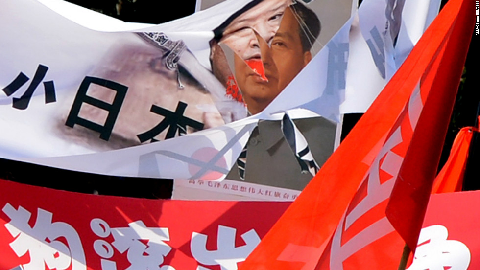 Protests swept through China as citizens expressed their anger at Japan's island purchase. A shredded banner shows Japanese Prime Minister Yoshihiko Noda beside a picture of Mao Zedong during protests in Beijing on September 16, 2012.