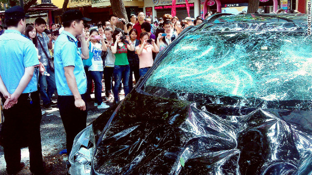 People take pictures of a Japanese car damaged during a Chinese protest last month.