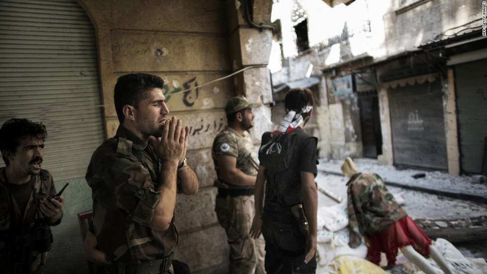 "A Free Syrian Army fighter yells ""Allahu Akbar!"" (Arabic for ""God is great!"") as he mans a position with his comrades Sunday in Aleppo, Syria's largest city."