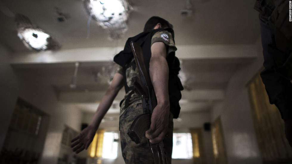 A Free Syrian Army fighter moves inside an artillery-shelled mosque Sunday in Aleppo.
