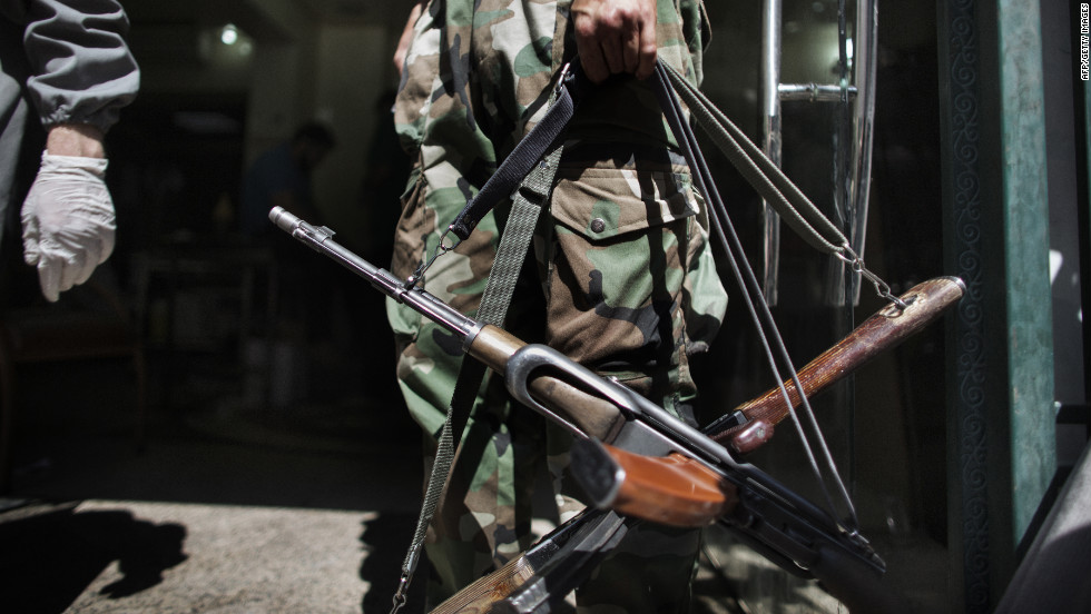 A Syrian rebel holds AK-47 rifles belonging to wounded comrades at the entrance to an Aleppo hospital on Tuesday.