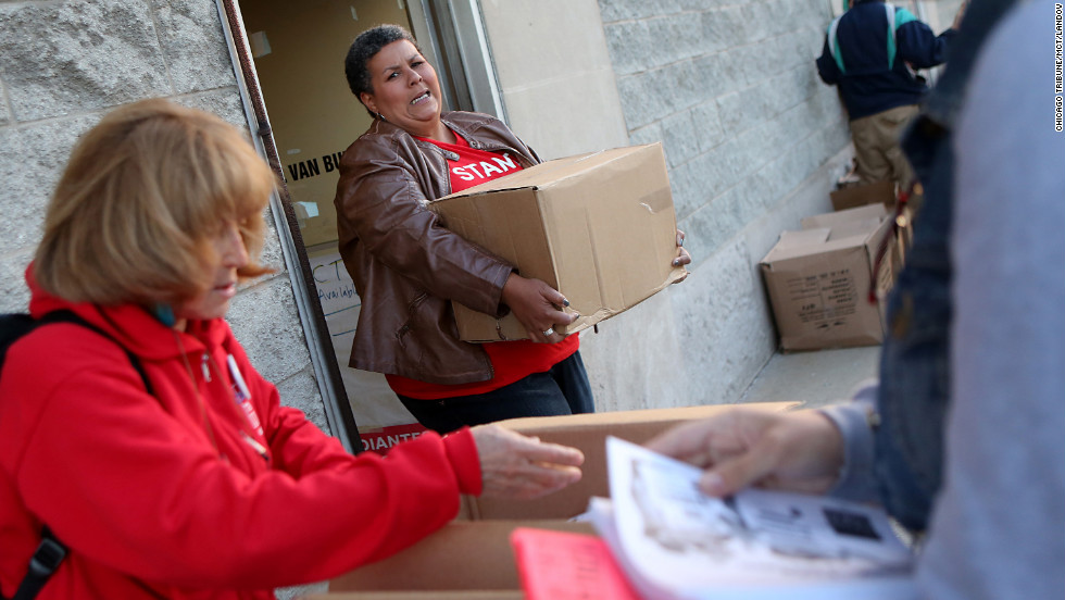 American Federation of Teachers organizer Samantha Jordan, center, carries a box of informational papers for distribution outside of protest locations in Chicago on Tuesday.
